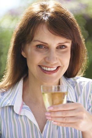 causcasian: Middle Aged Woman Enjoying Glass Of White Wine Stock Photo