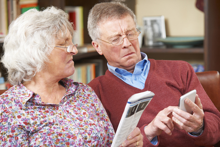 confusion: Confused Senior Couple Trying To Operate Mobile Phone