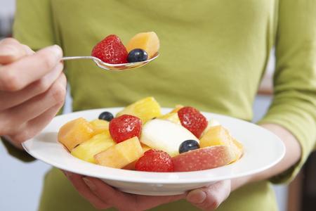 comiendo: Cerca de la mujer de comer del plato de fruta fresca Foto de archivo