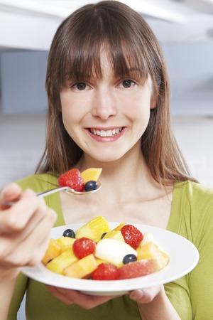 ensalada de frutas: Mujer joven que come el plato de fruta fresca