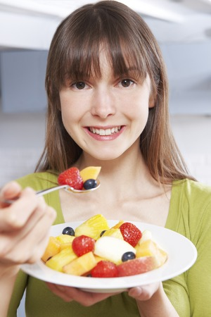 healthy snack: Young Woman Eating Bowl Of Fresh Fruit Stock Photo