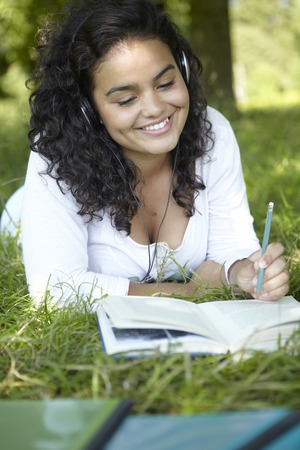 revising: Carefree Student Revising And Listening To Music In Park