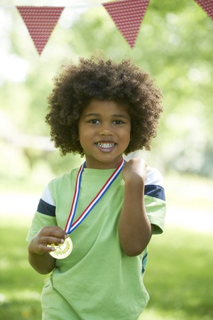 sports day: Young Boy Winning Medal At Sports Day