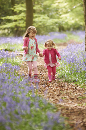 galoshes: Two Girls Running Through Bluebell Woods Together Stock Photo