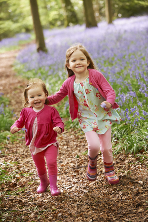 bluebell woods: Two Girls Running Through Bluebell Woods Together Stock Photo