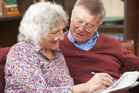 Senior Couple Doing Crossword Puzzle In Newspaper Together Stock Photo