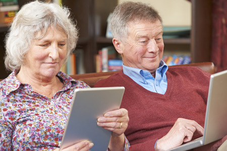 silver surfer: Senior Couple Using Digital Tablet And Laptop At Home Stock Photo