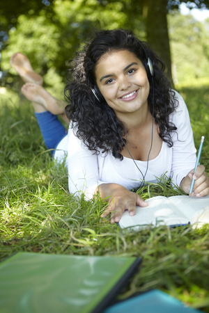 revising: Female Student Revising And Listening To Music In Park