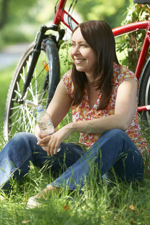 cycle ride: Middle Aged Woman On Cycle Ride In Countryside Stock Photo
