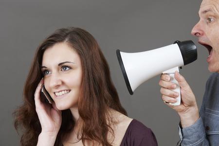 padre e hija: Frustrado Padre Grita En hija adolescente en el teléfono móvil a través de