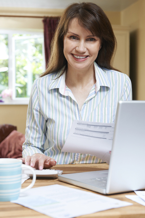 home finances: Smiling Middle Aged Woamn Looking At Home Finances