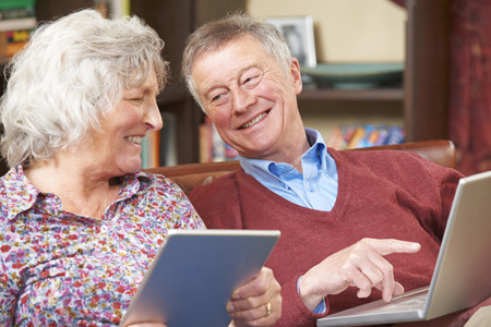 tablet computer: Senior Couple Using Digital Tablet And Laptop At Home Stock Photo