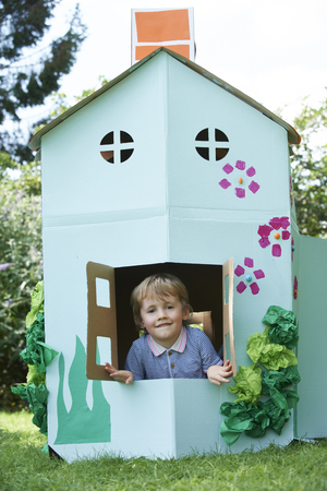 Young BoyPlaying In Home Made Cardboard House Banco de Imagens