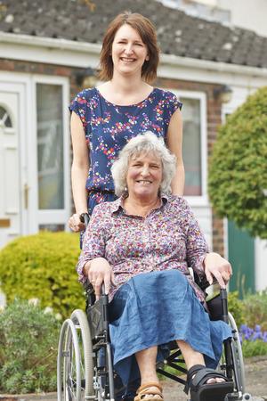 empujando: La hija adulta empuja a la madre en silla de ruedas