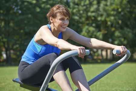 rowing: Mature Woman Exercising On Rowing Machine In Park