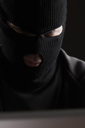 criminal: Masked Criminal Accessing Computer Data