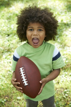 3 year old boy: Excited Young Boy Playing American Football In Park