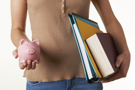 college fund savings: Female Student Holding Textbooks, Files And Piggy Bank