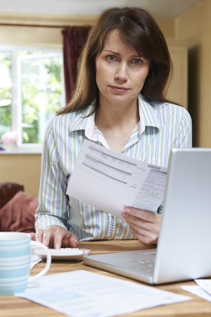 home finances: Worried Middle Aged Woman Looking At Home Finances