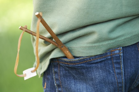 aggression: Close Up Of Slingshot In Boys Trouser Pocket