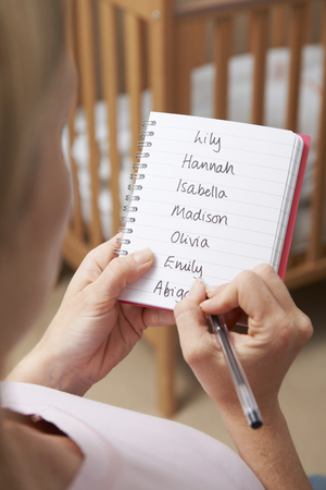 unrecognisable people: Woman Writing Possible Names For Baby Girl In Nursery