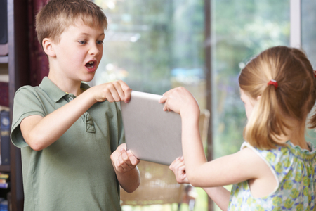 sibling rivalry: Boy And Girl Fighting Over Digital Tablet At Home Stock Photo