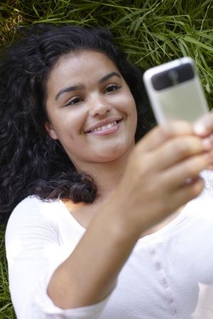 sending: Young Woman Lying On Grass Sending Text Message