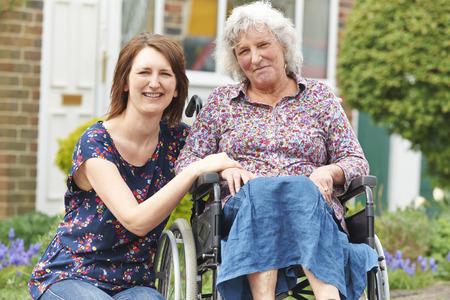 paraplegico: La hija adulta con la madre en silla de ruedas