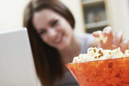 personas comiendo: Mujer que come las palomitas mientras que ve la película en el ordenador portátil
