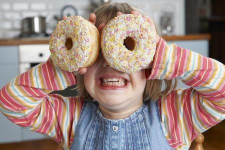 sugary: Girl Making Glasses Using Sugary Doughnuts Stock Photo
