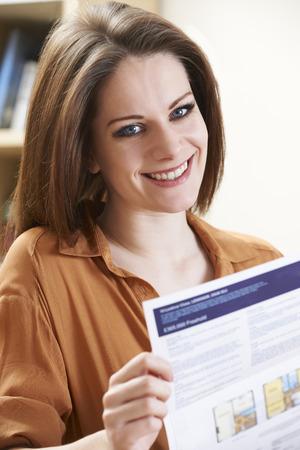 persona leyendo: Sonrisa de la mujer joven que estudia Estate Los datos de socios para el nuevo hogar Foto de archivo