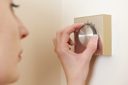 thermostat: Woman Adjusting Central Heating Thermostat Control