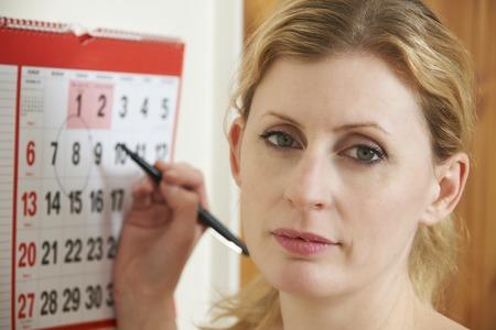 Worried Woman Circling Date On Calendar