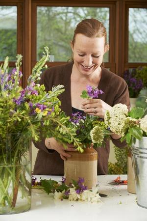 arranging: Florist Working On Arrangement In Shop Stock Photo