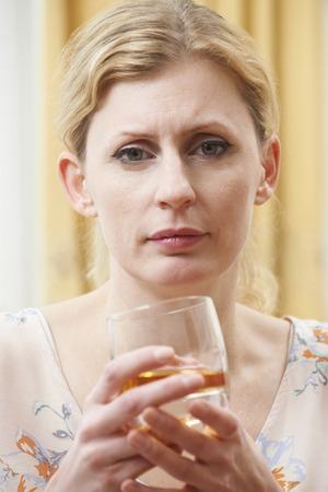 femme triste: Femme tenant un verre de whisky