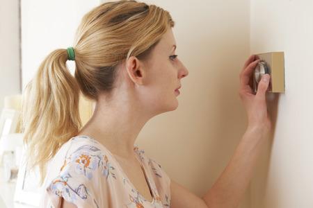 adjusting: Woman Adjusting Central Heating Thermostat Control