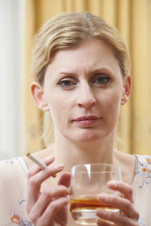 mujer triste: Mujer con vaso de whisky y de cigarrillo Foto de archivo