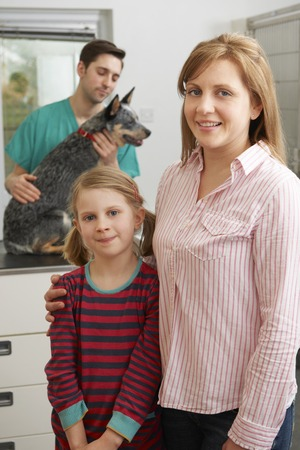 7 year old girl: Mother And Daughter Taking Dog For Examination At Vets Stock Photo