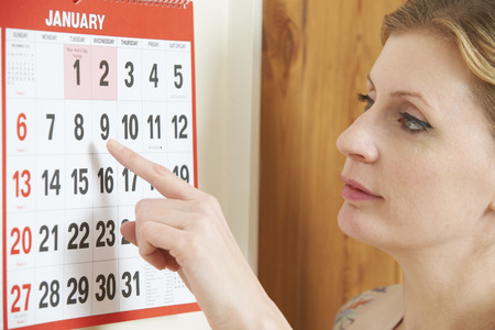 Worried Woman Looking At Date On Calendar Фото со стока