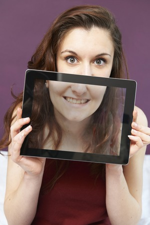 mouth smile: Smiling Teenage Girl Holding Digital Tablet In Front Of Face Stock Photo