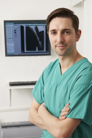 medical professional: Veterinary Surgeon Standing In Front Of X Ray Stock Photo