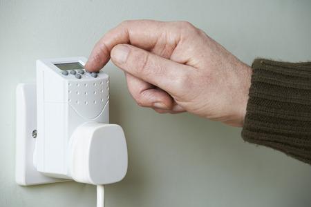 plug in: Close Up Of Hand Adjusting Timer Switch In Plug Socket