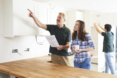 新しい台所のための計画を見て大工を持つ女性