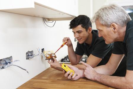 aprendizaje: Electricista con Aprendiz Trabajo En Nuevo Hogar Foto de archivo