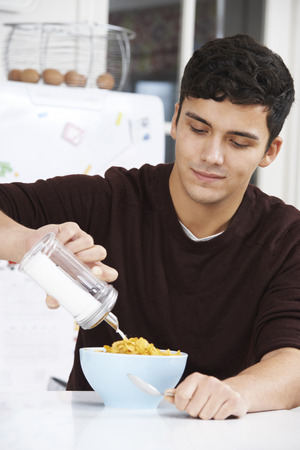 hypertensive: Young Man Adding Sugar To Breakfast Cereal Stock Photo
