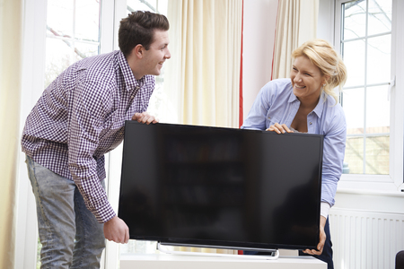 unwrapping: Excited Couple Setting Up New Television At Home