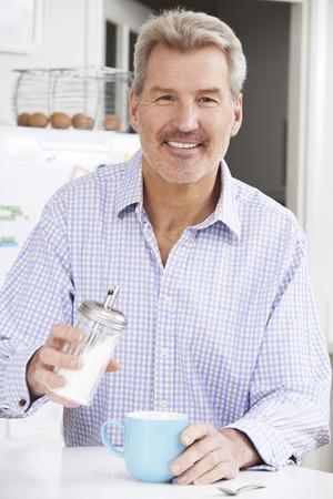 adding: Mature Man Adding Sugar to Cup Of Coffee