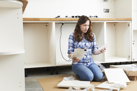 self assembly: Frustrated Woman With Self Assembly Furniture In Kitchen Stock Photo