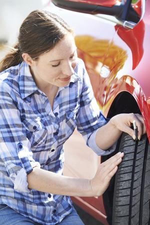 banda de rodamiento: Mujer que controla la banda de rodadura de los neum�ticos en el coche con man�metro