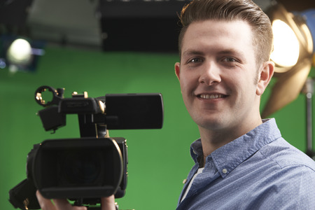video camera: Male Camera Operator In Television Studio
